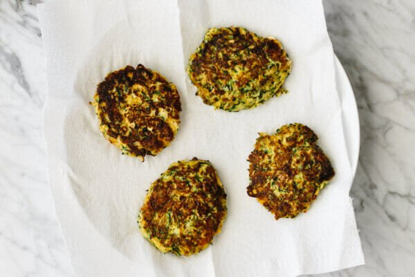Zucchini fritters on a paper towel lined plate.