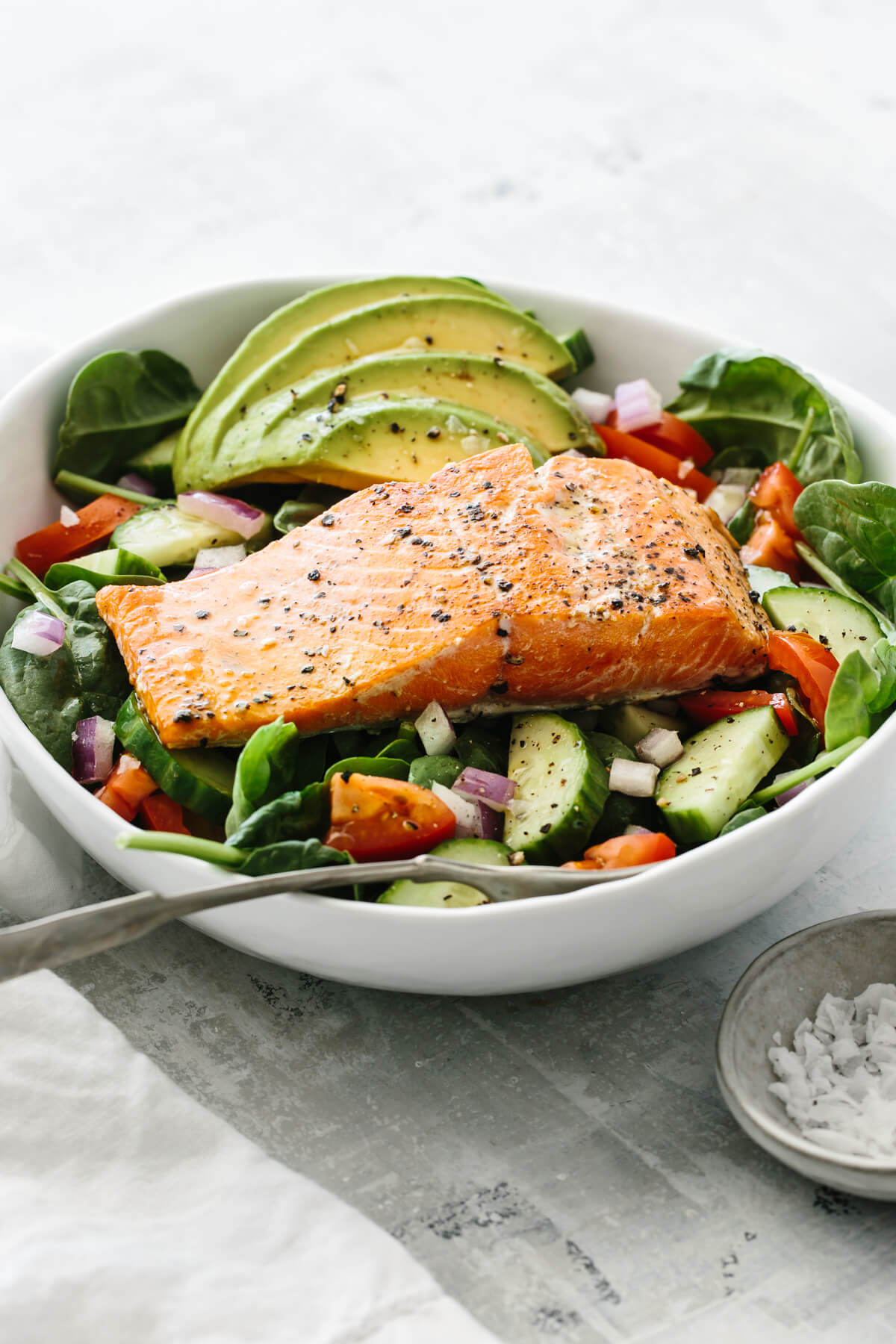 Salmon placed on top of salad recipe with avocado and other ingredients.