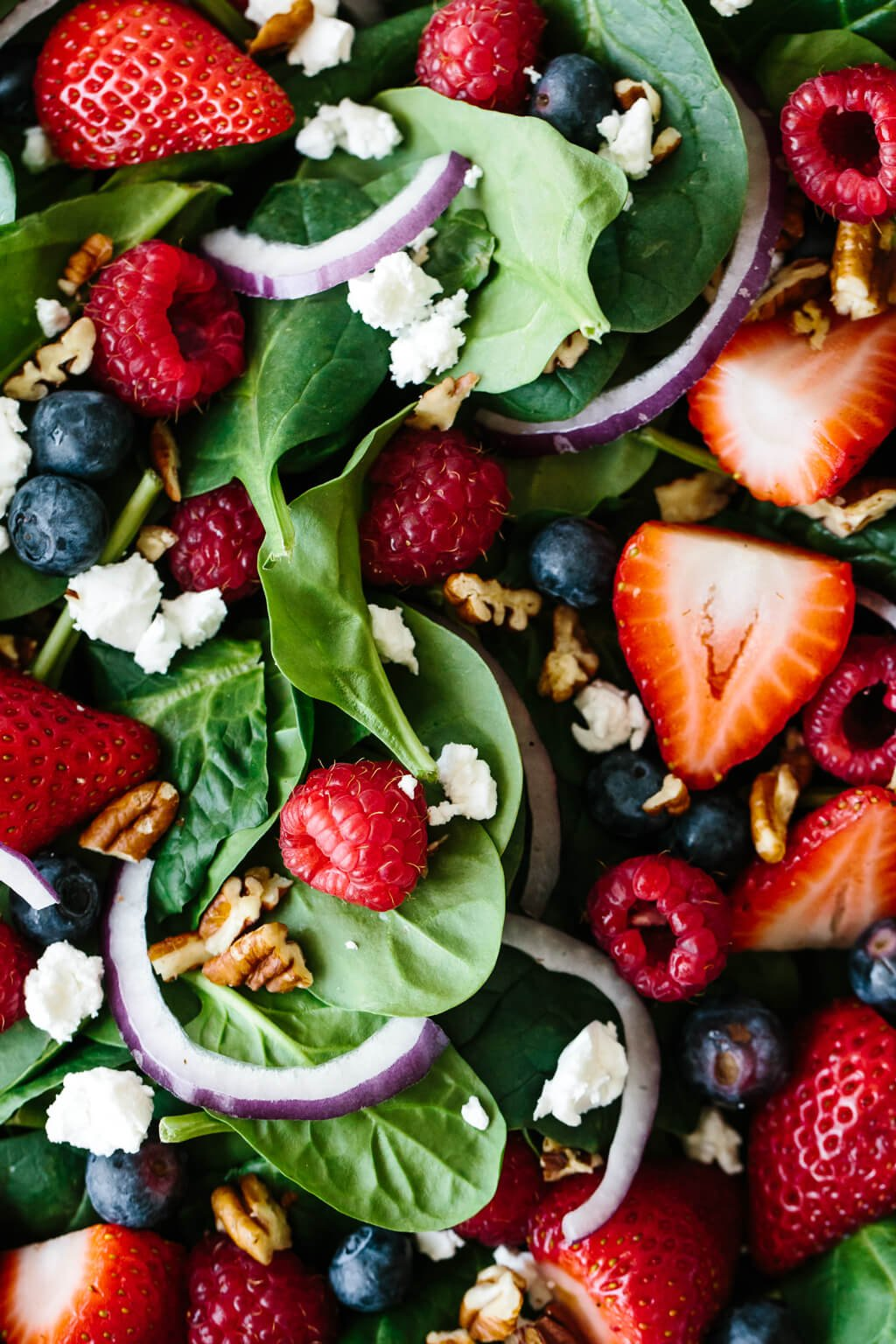 Close up photo of berry spinach salad.