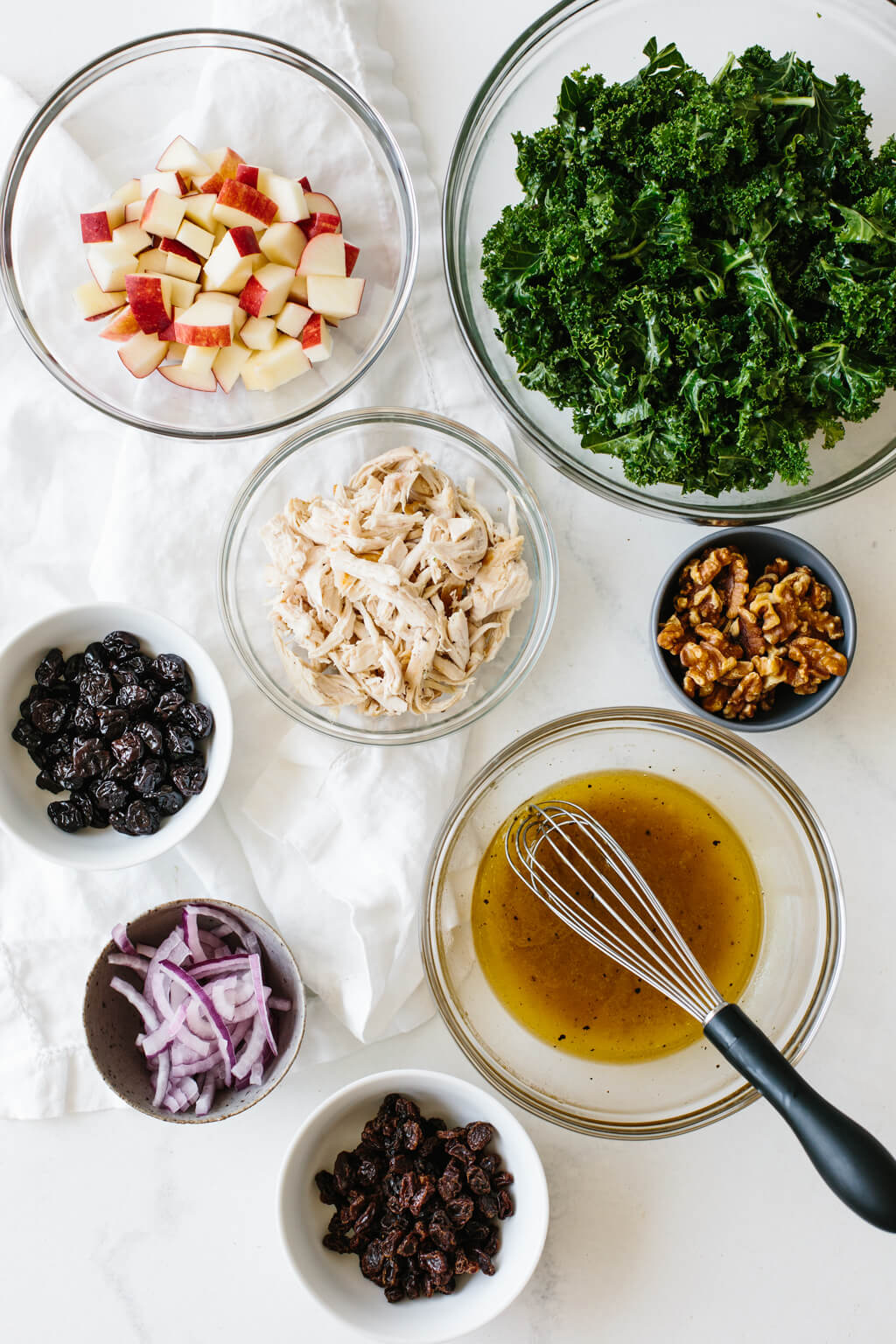 Ingredients for the kale salad recipe in individual bowls on a table.
