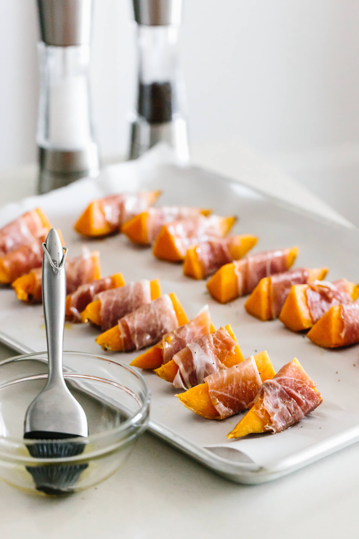 Prosciutto wrapped sweet potatoes all lined up on a baking sheet, ready to be baked.
