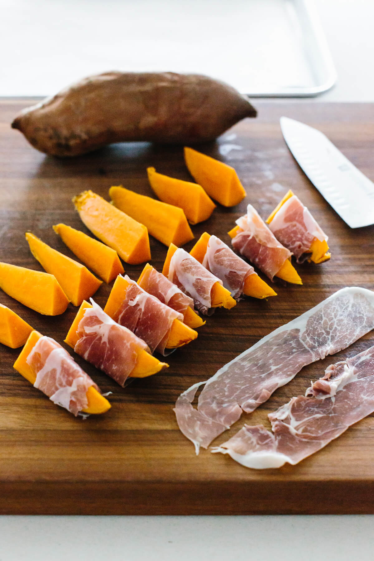 Slicing prosciutto in half and wrapping sweet potato slices.