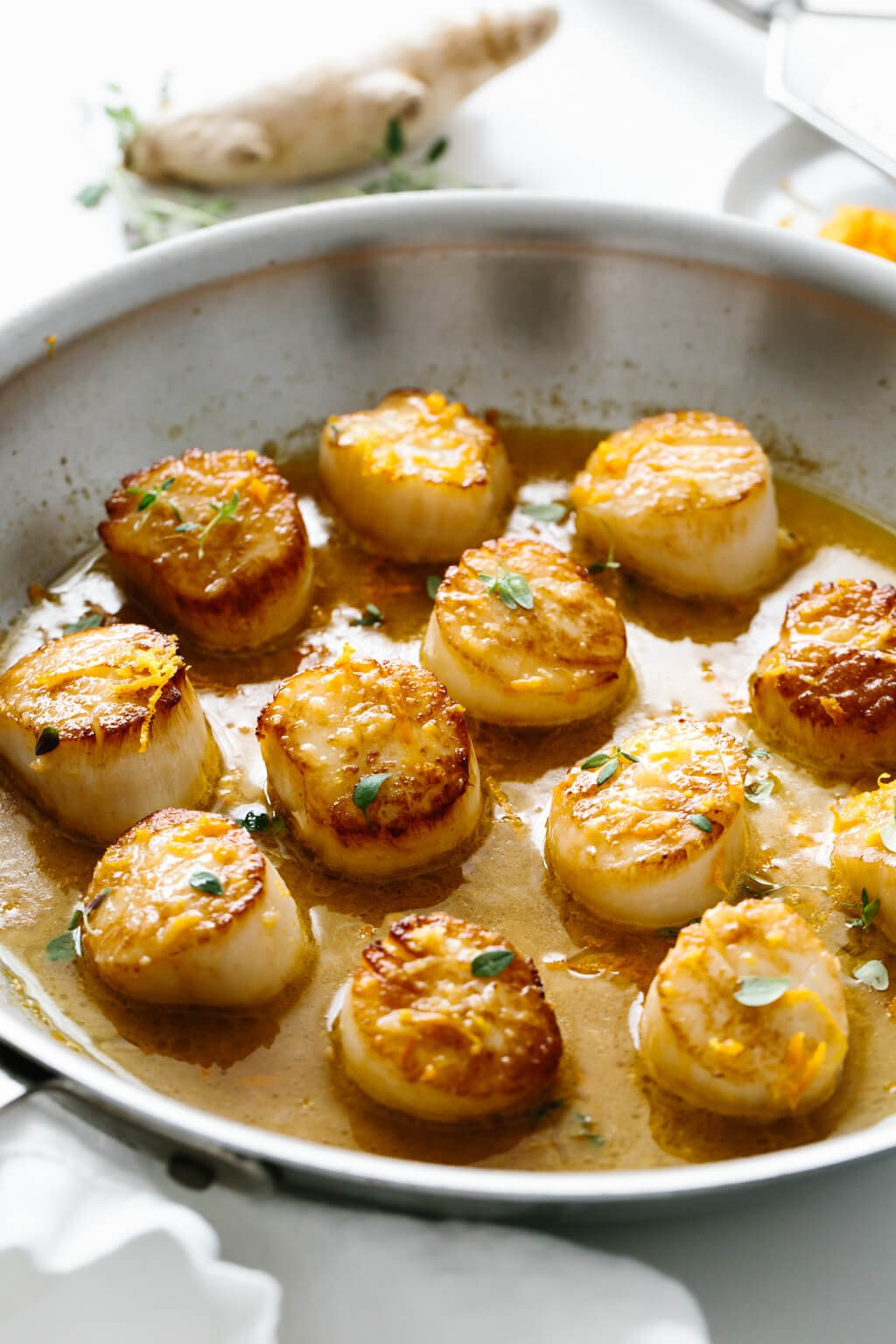 Several scallops in a pan.