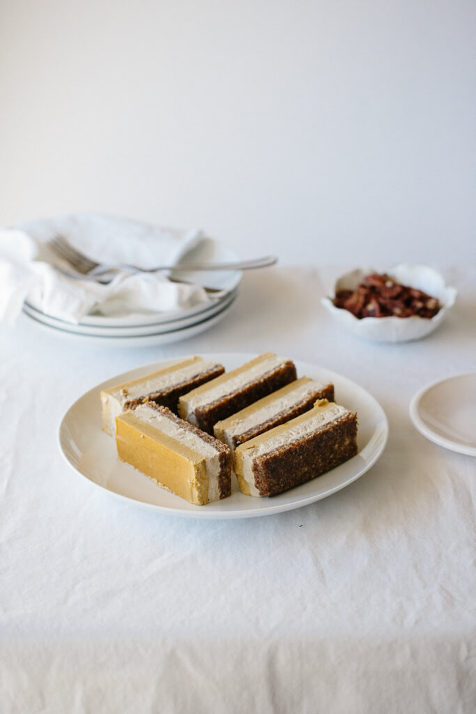 This raw white chocolate and pumpkin cheesecake will keep all your guests happy! It's healthy, gluten-free, vegan and paleo - with all the flavors of the season. www.downshiftology.com