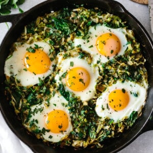 Green shakshuka in a cast iron pan.