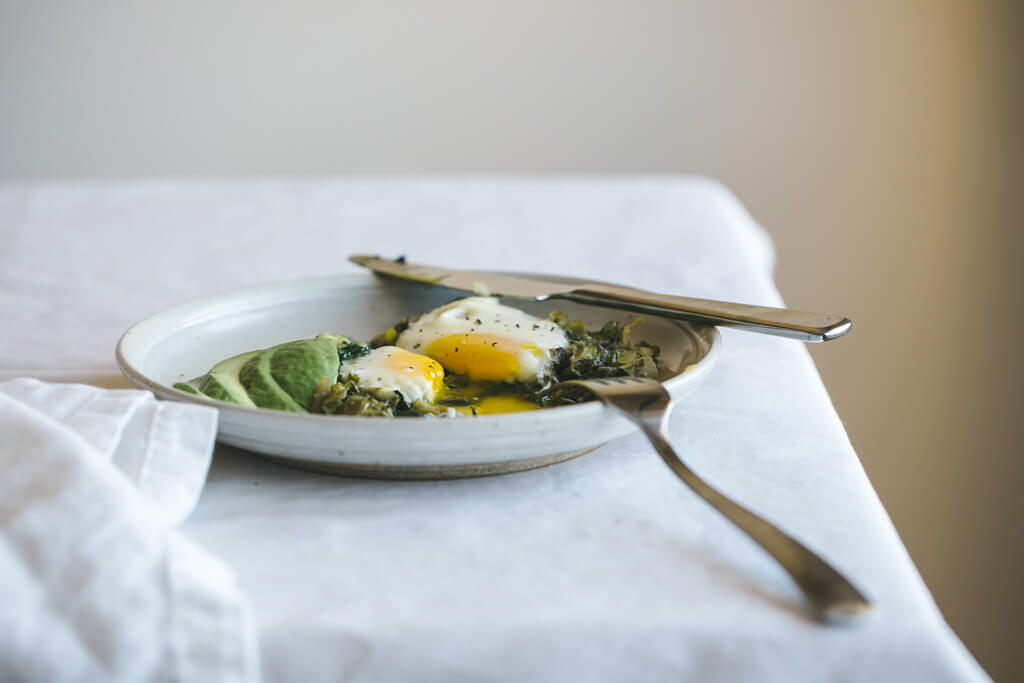 Green shakshuka with shaved brussels sprouts and spinach.