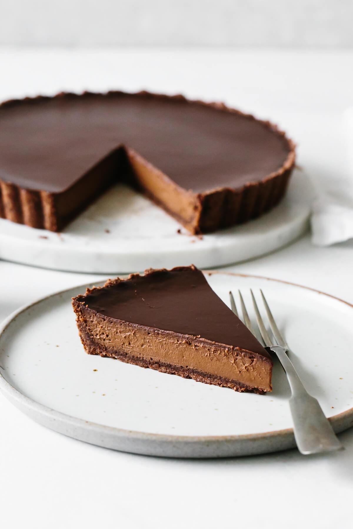 A single slice of chocolate tart on a plate.