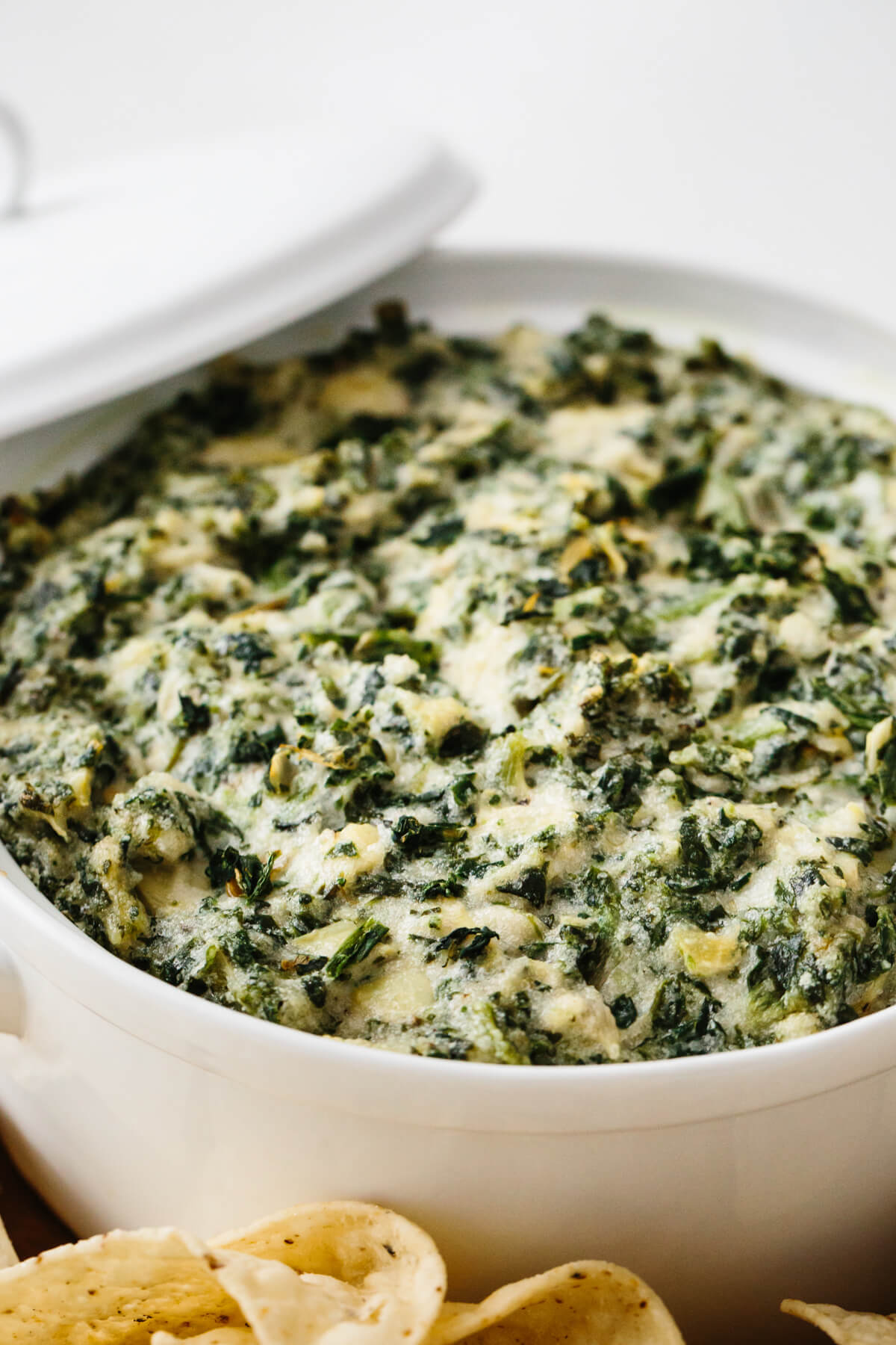 Spinach artichoke dip in a white casserole dish.