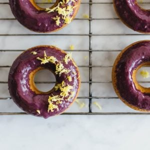 (gluten-free, paleo) Baked lemon donuts with blackberry glaze.