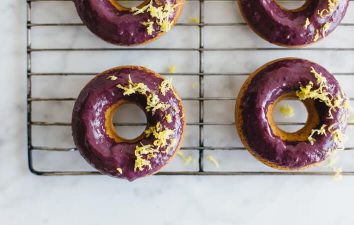 (gluten-free, paleo) Baked lemon donuts with blackberry glaze.