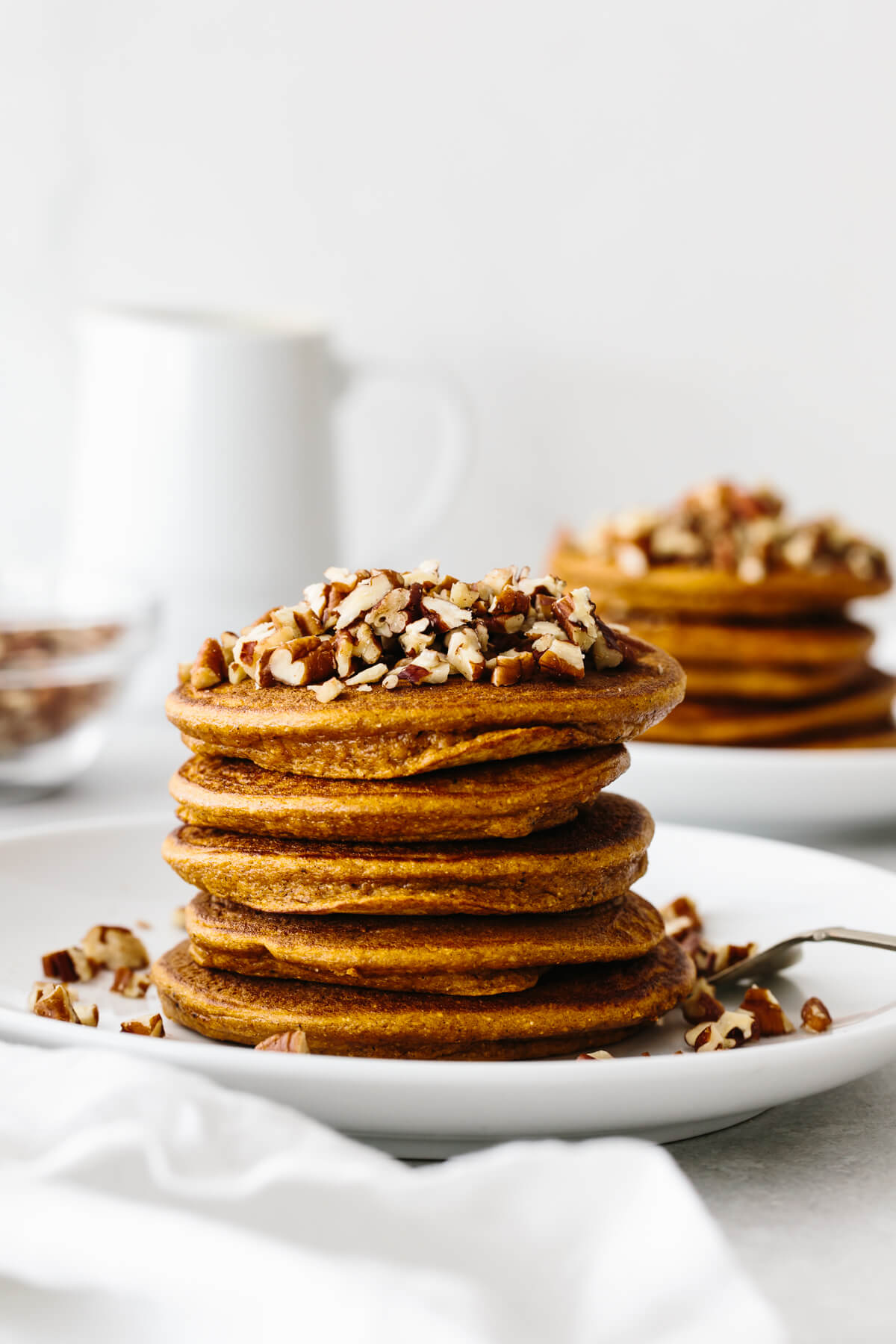 A stack of paleo pumpkin pancakes on a plate, topped with chopped pecans.