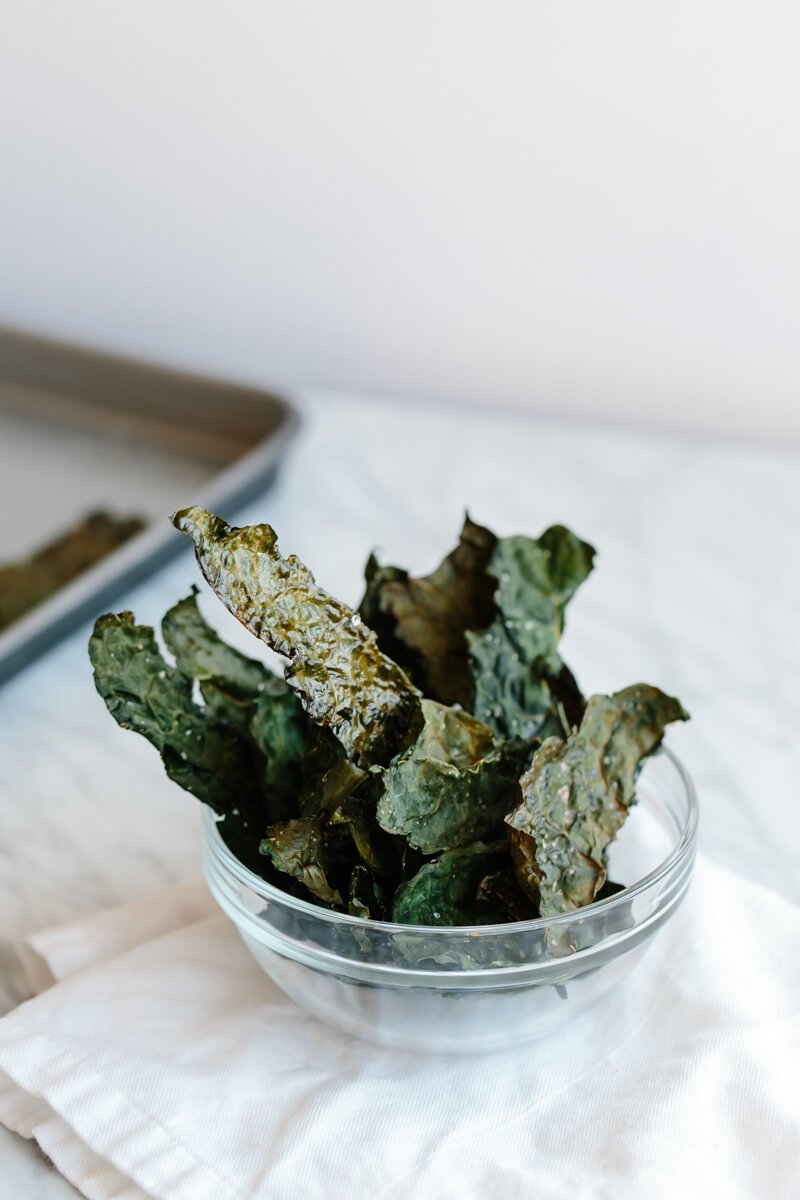 How to make crispy kale chips. A healty snack that's super easy to make and satisfies all your salty and savory cravings. www.downshiftology.com