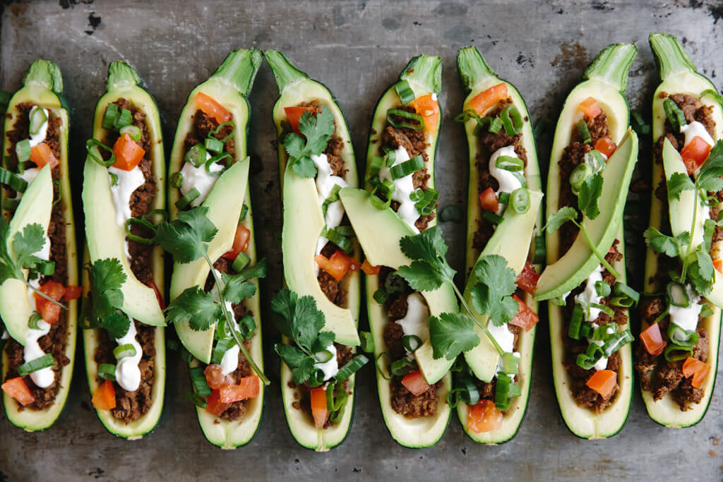 Taco stuffed zucchini boats lined up next to each other.