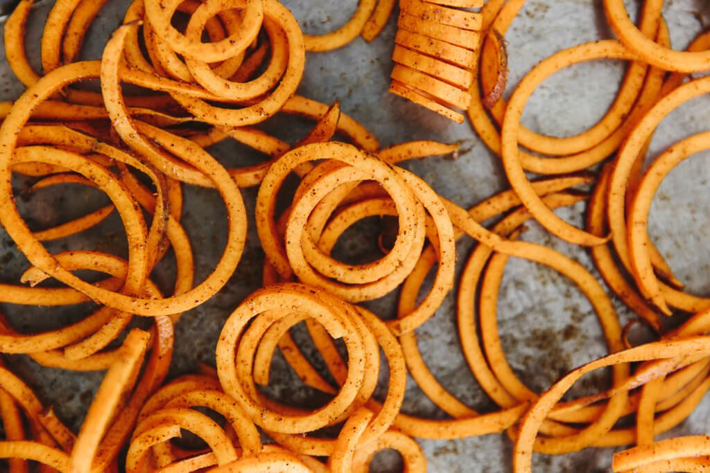 (gluten-free, paleo) Curly sweet potato fries are easily made with a spiralizer. They're seasoned with paprika and garlic powder and baked in the oven until perfectly crispy.