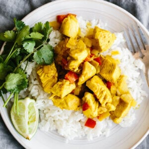 Coconut curry chicken on a bed of rice on a plate.