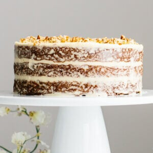 Gluten-free carrot cake on a cake stand with frosting.