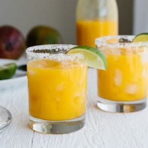 Two mango margaritas in glasses with a lime wedge.