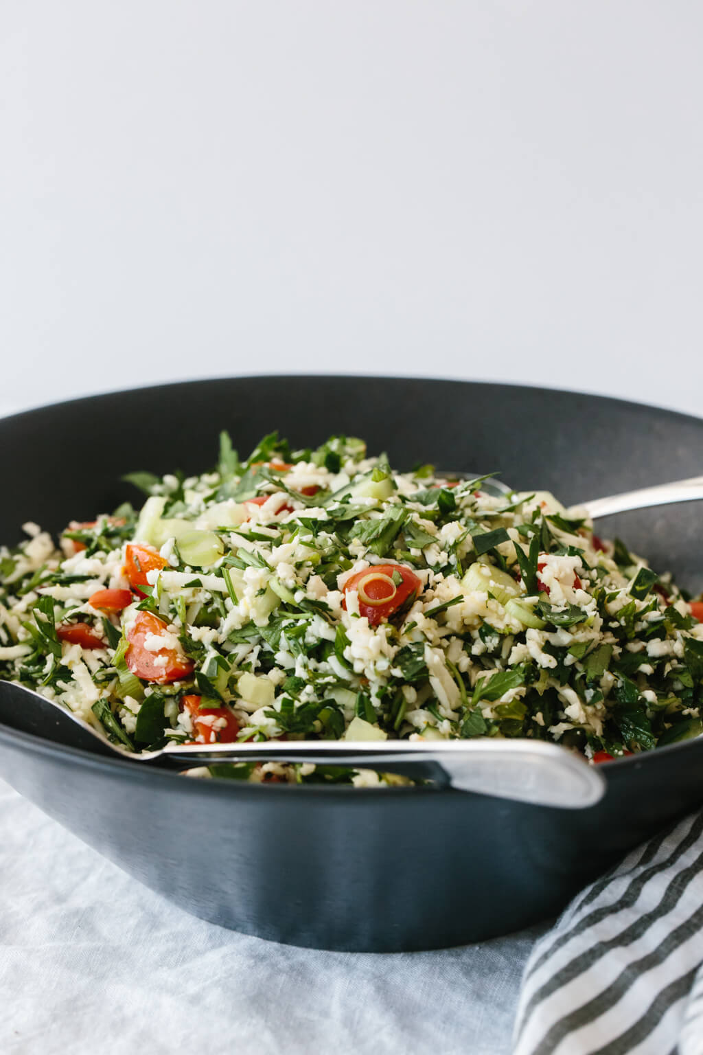 (gluten-free, paleo, whole30) Cauliflower rice tabbouleh is a tasty spin on tabbouleh and swaps bulgur with cauliflower rice, making this lemon herb salad gluten-free and paleo-friendly.