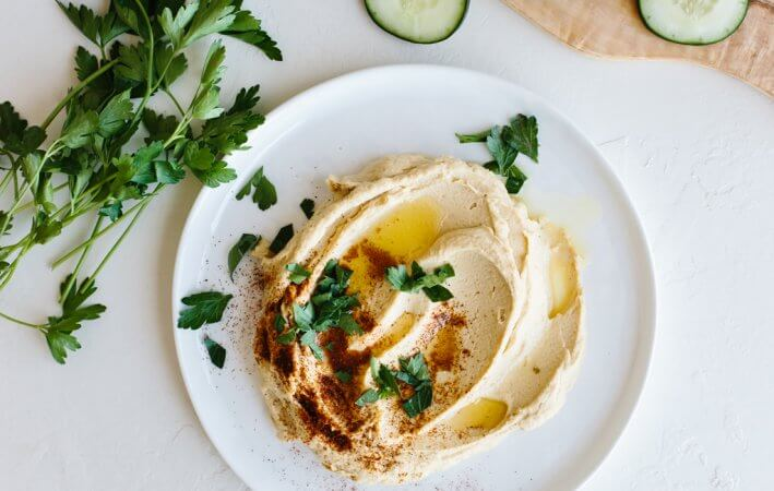 A healthy, homemade hummus recipe that's super easy - it comes together in less than 3-minutes! It also tastes better than anything you can buy in the store.