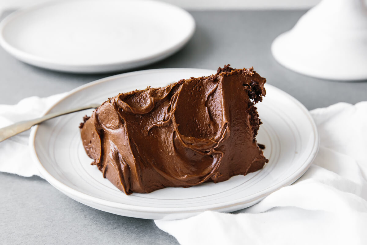 A single slice of paleo chocolate cake on a white plate.