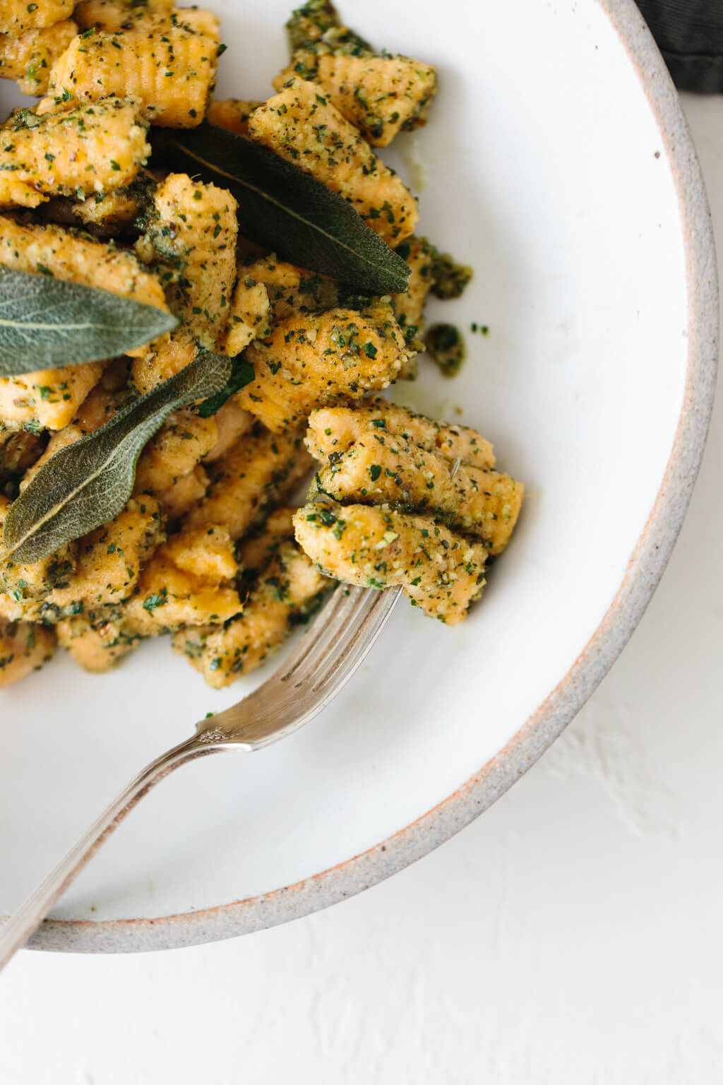 (gluten-free, paleo) Sweet potato gnocchi topped with a delicious sage walnut pesto. It's the perfect hearty and savory meal for fall and winter.