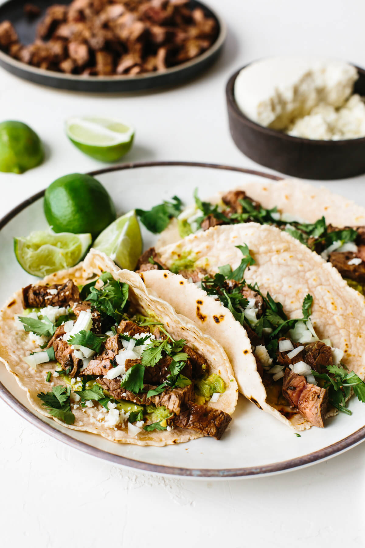 A plate with carne asada tacos next to limes.