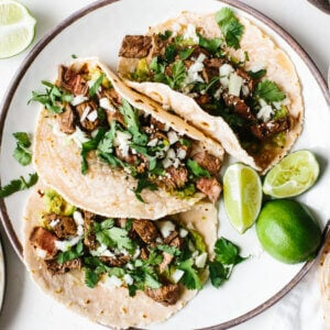 A plate of carne asada tacos next to tortillas and cheese.