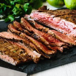 Carne asada sliced into pieces on a cutting board.