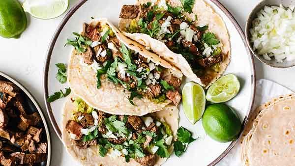 Carne asada tacos on a plate with limes and carne asada.