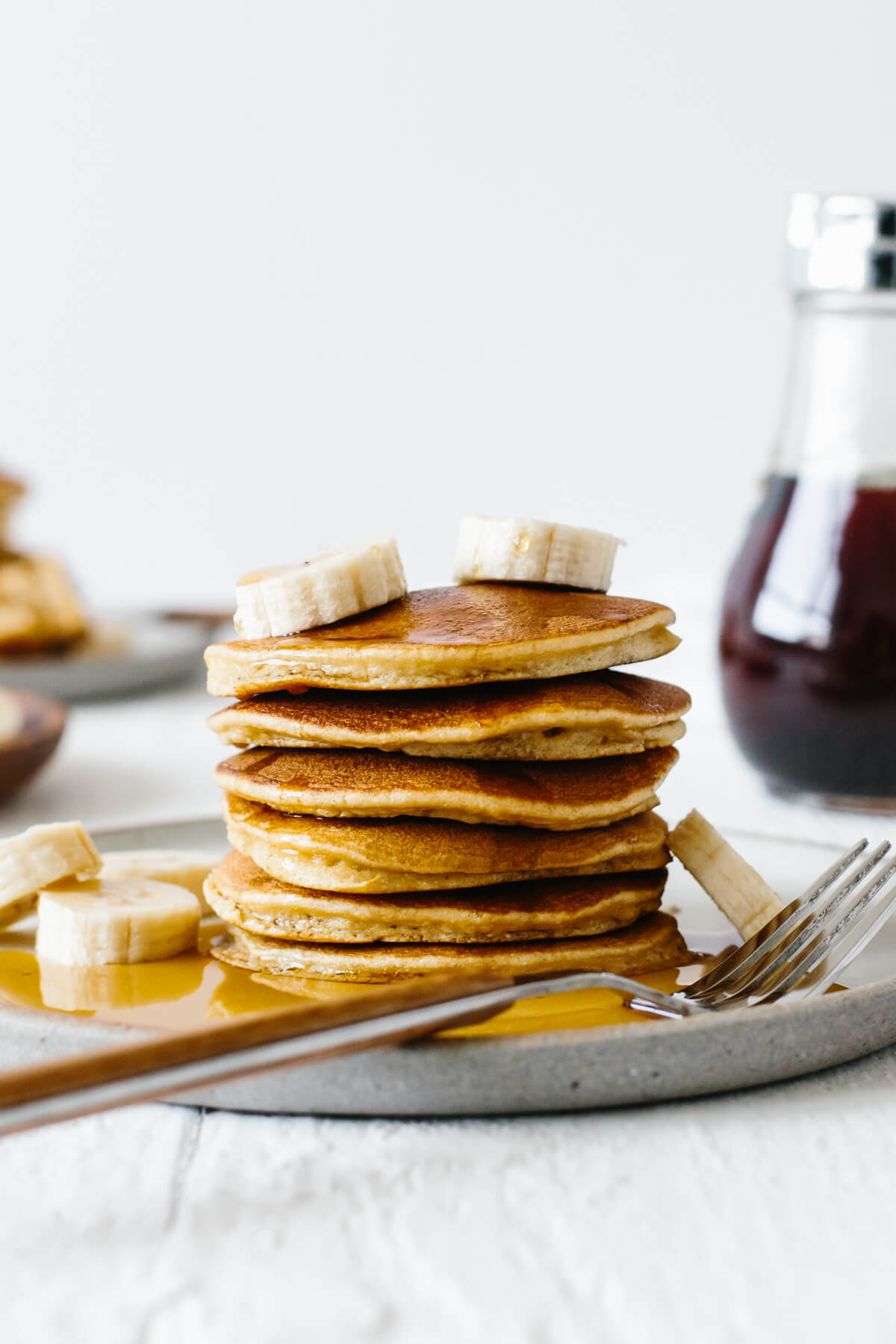 Stack of paleo pancakes on a plate with sliced bananas and syrup.