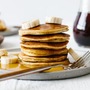 Stack of paleo pancakes on a plate with bananas and syrup.