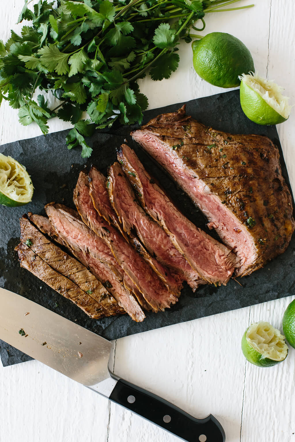 Carne asada steak sliced into pieces on a cutting board, next to limes and cilantro.