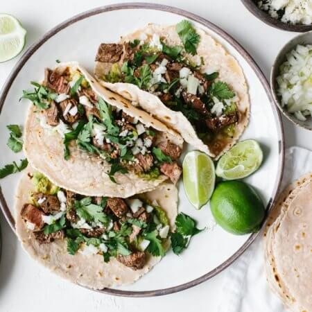 These delicious carne asada tacos are made with grilled skirt steak, avocado, cotija cheese, chopped onion and fresh cilantro. They're super flavorful steak street tacos.