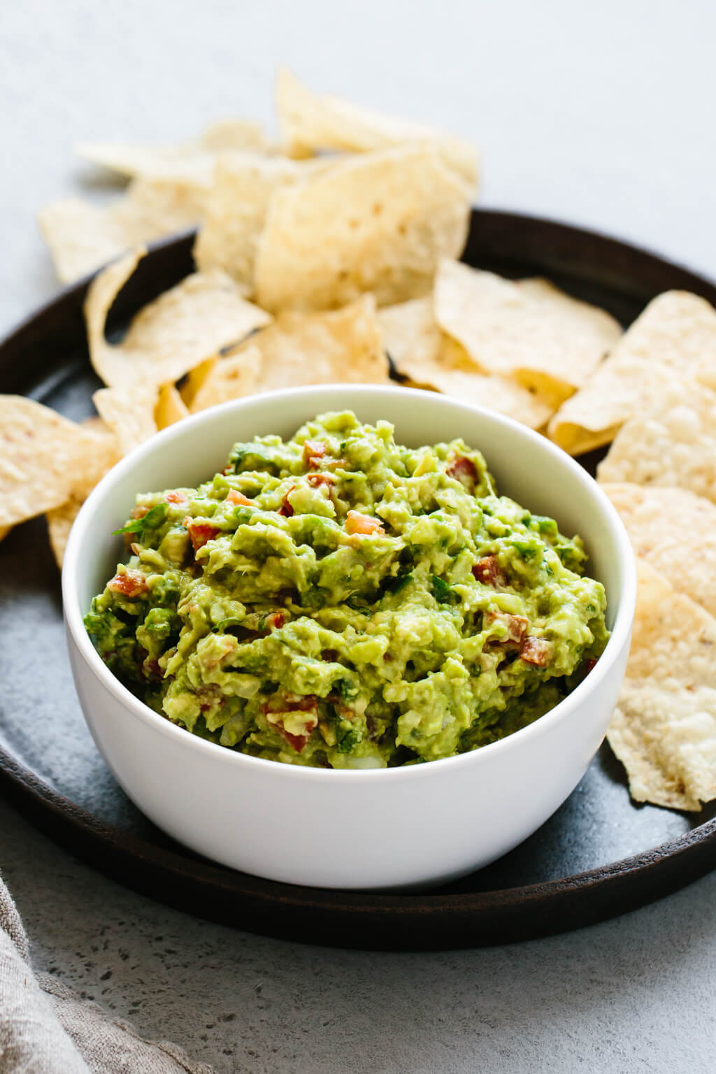 Guacamole in a bowl surrounded by chips.