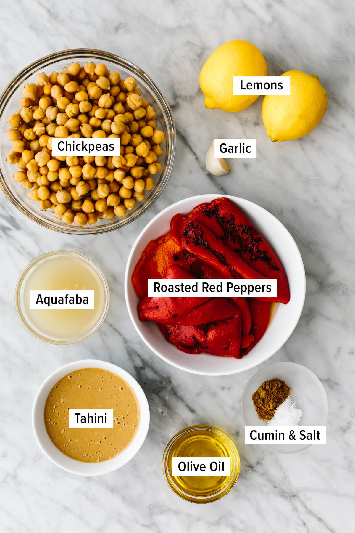 Ingredients for roasted red pepper hummus on a table.