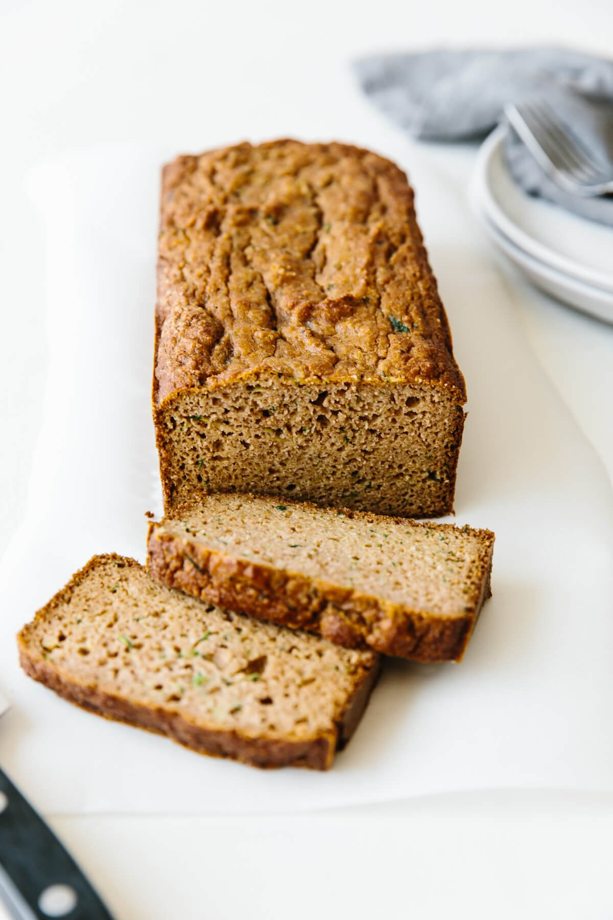 Paleo zucchini bread on a table with two slices from the loaf.