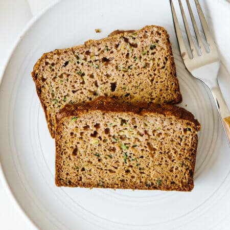 Two slices of paleo zucchini bread on a white plate.