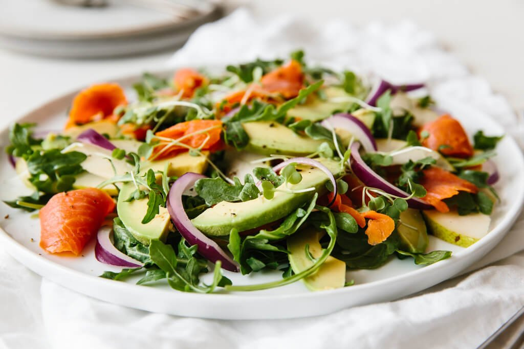 An easy and delicious arugula salad recipe made with baby arugula, smoked salmon, avocado, pear and red onion.