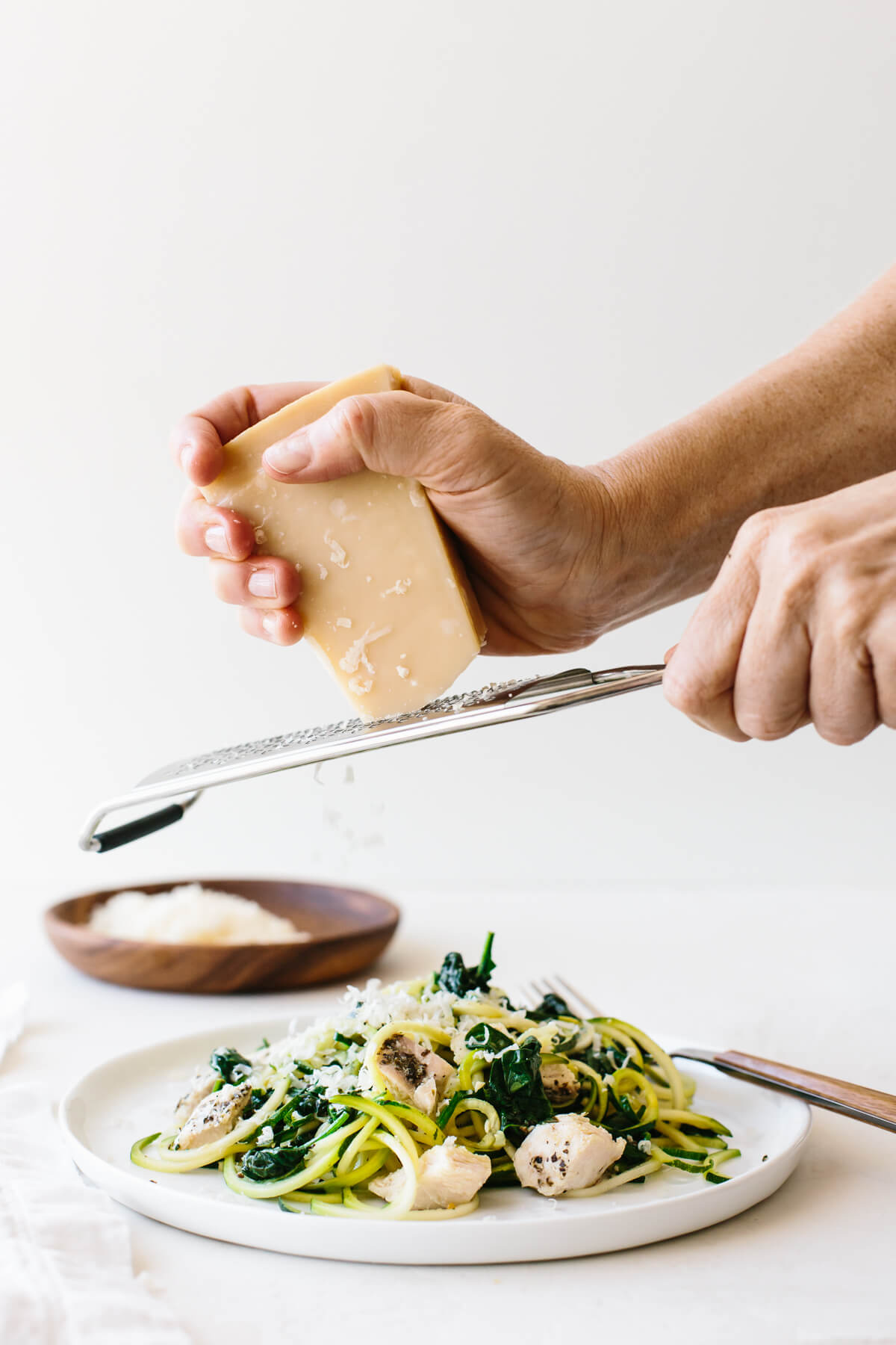 Grating fresh parmesan on a plate of zucchini noodles and chicken.