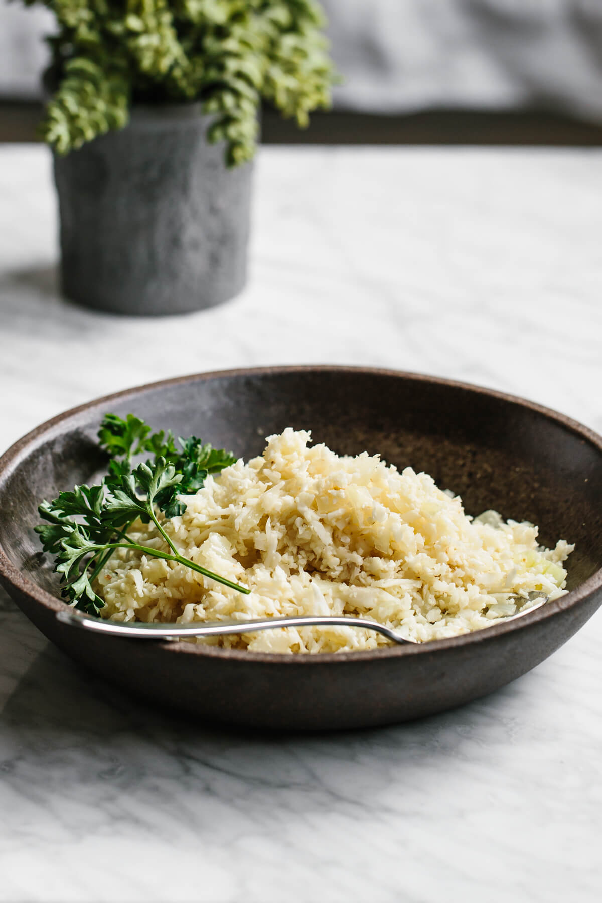 Cauliflower rice in a bowl with herbs.