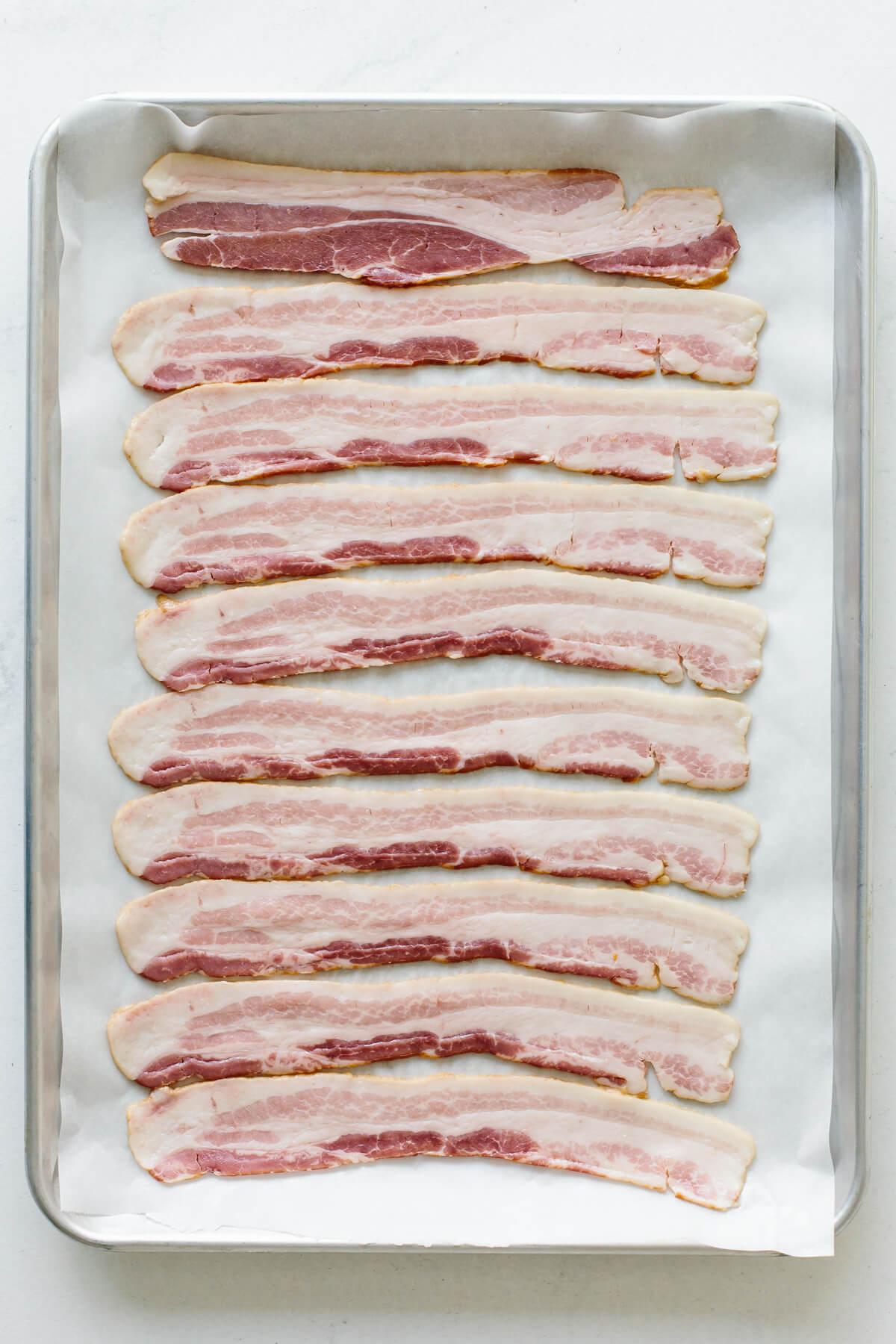 Raw bacon on a sheet tray.