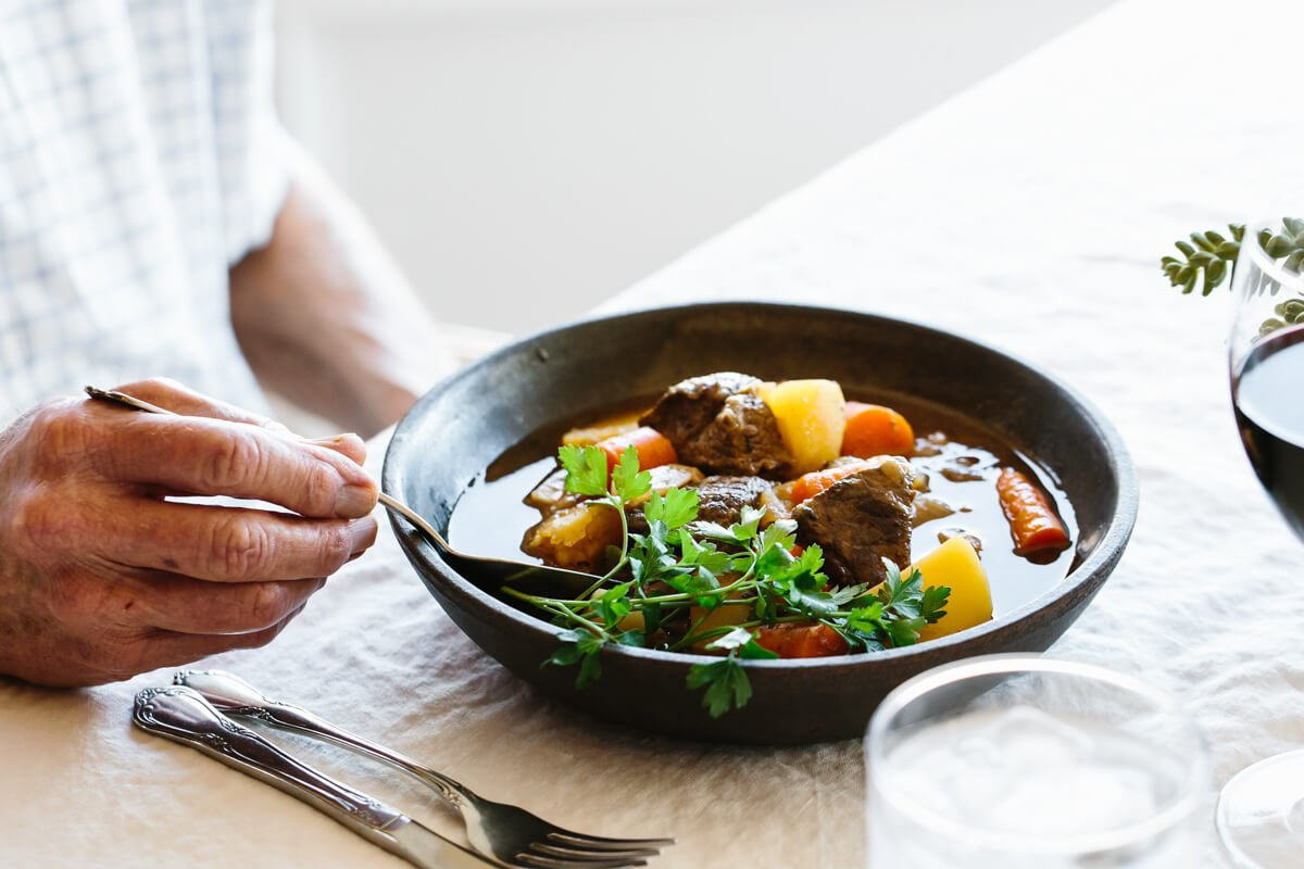 Eating lamb stew in a bowl.