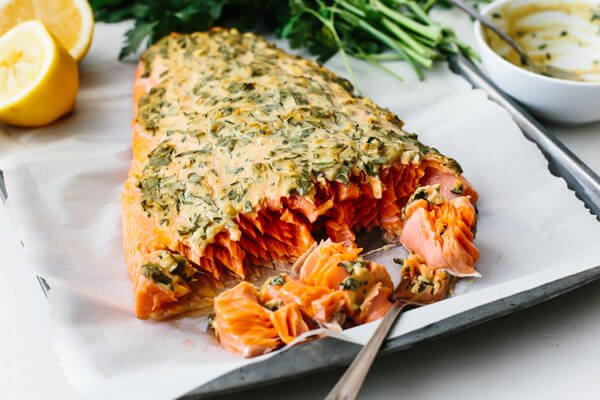 Whole fillet of dijon baked salmon with a fork.