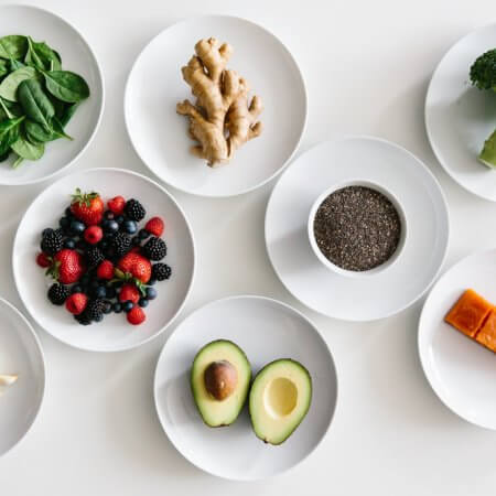 Eight plates of individual anti-inflammatory ingredients on white table.