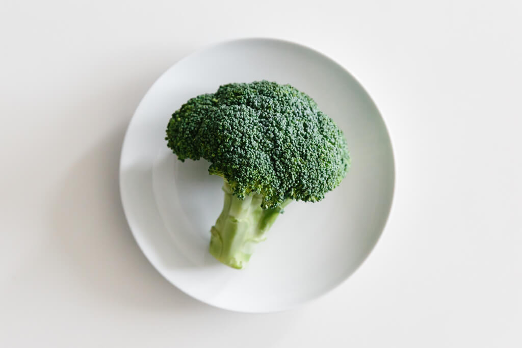 Plate of broccoli on a white table.