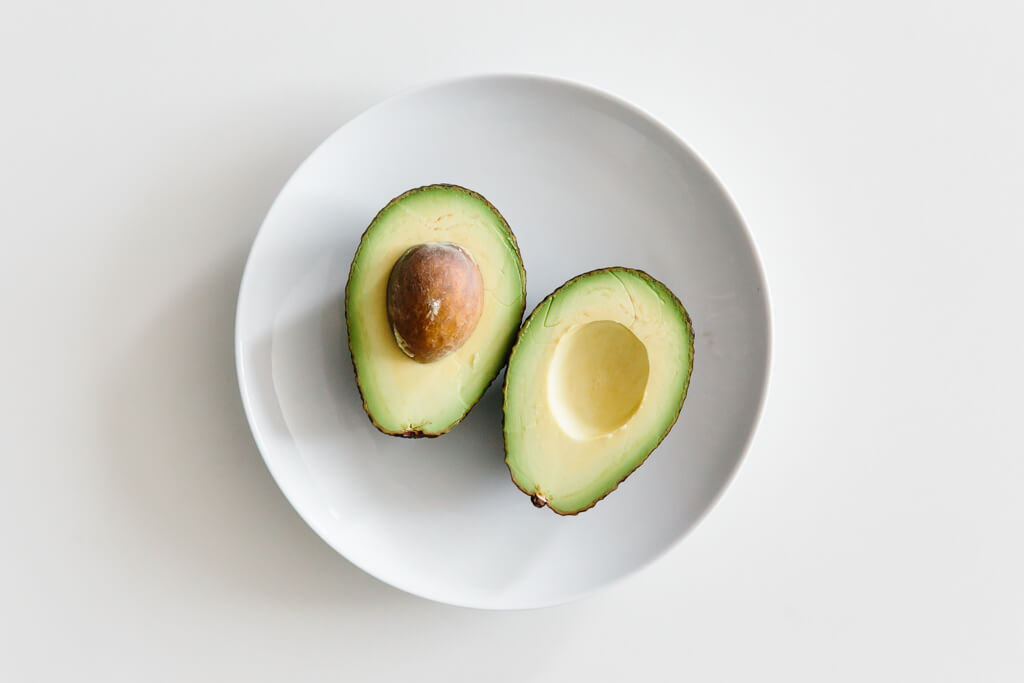 Plate of avocado sliced in half on a white table.