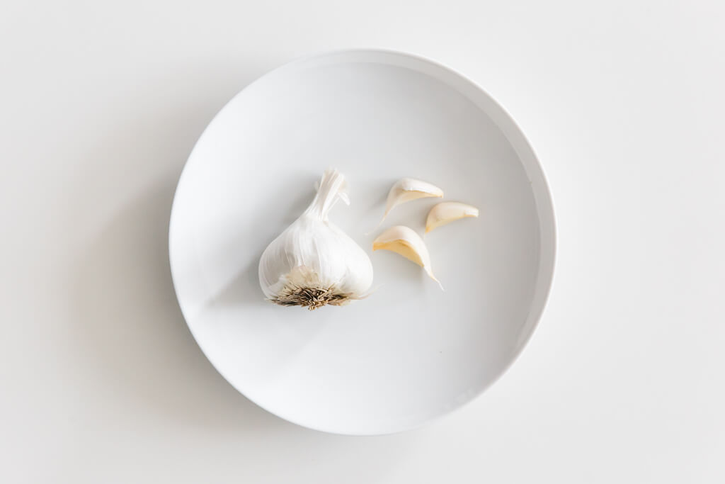 Plate of garlic on a white table.