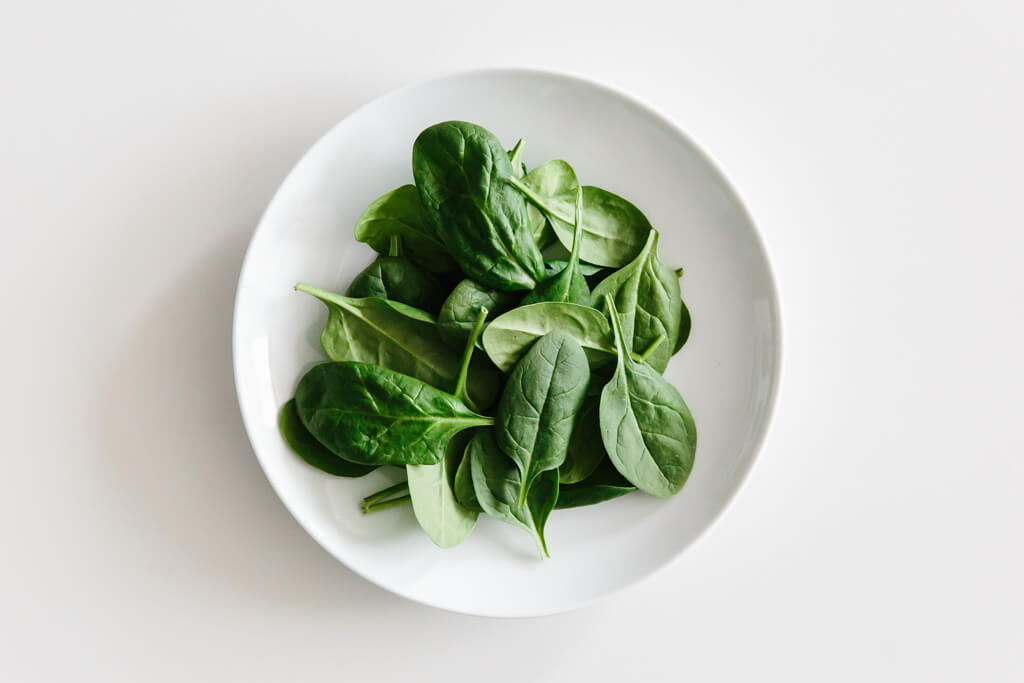 Plate of spinach on a white table.