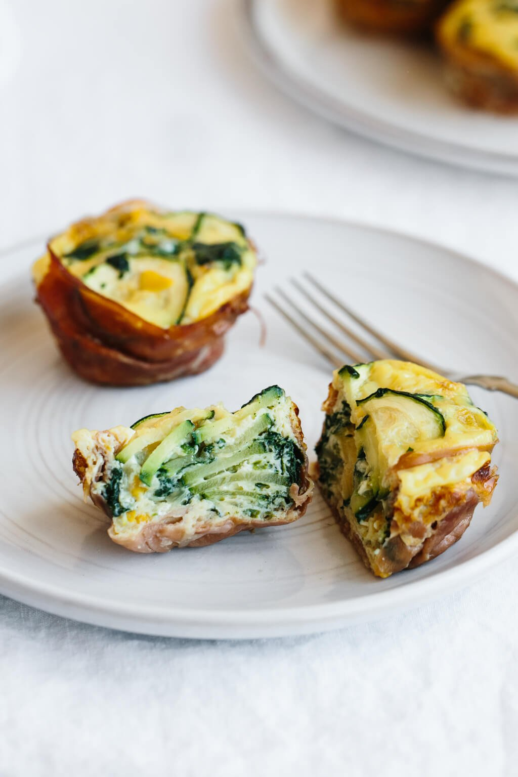 An egg muffin sliced in half to show the zucchini inside.