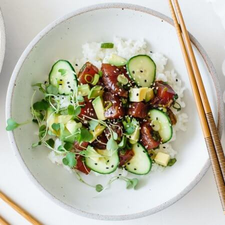 Poke bowl is easy to make at home. This ahi poke bowl recipe is made with ahi tuna, a soy sauce marinade and sushi rice, then topped with cucumber, avocado, microgreens and sprinkled with sesame seeds. It's a healthy, gluten-free poke bowl recipe.